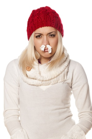 cold girl with paper stuffy nose on white background