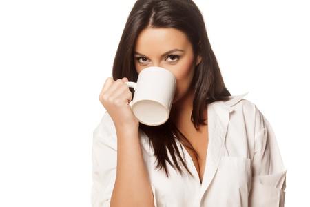 beautiful brunette in a white men s shirt drinking morning tea