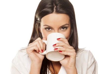 women holding cup: smiling beautiful brunette in a white men s shirt drinking coffee and showing his thumb
