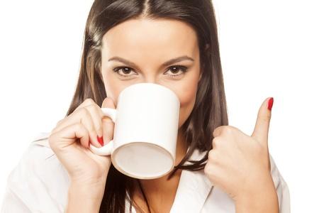 surpris belle brune dans une chemise blanche boit du thé et montre le pouce