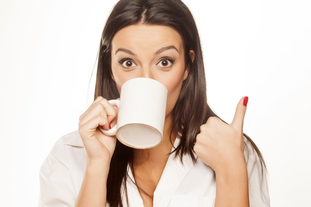 surprised beautiful brunette in a white shirt drinks tea and shows thumb Standard-Bild
