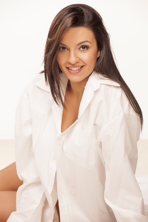 pretty smiling brunette in a white men s shirt Stock Photo