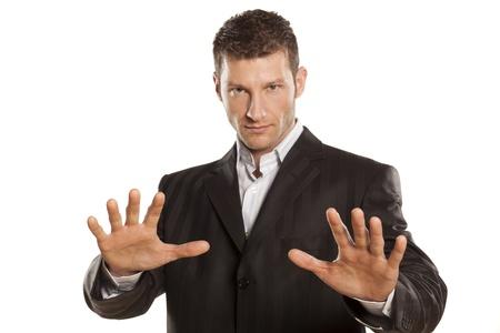 seguridad laboral: hombre de negocios serio con parada de manos colocadas en el fondo blanco Foto de archivo