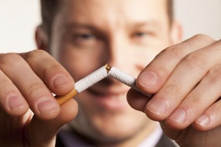 hombre fumando: sonriente hombre con una cara borrosa rompe un cigarrillo Foto de archivo