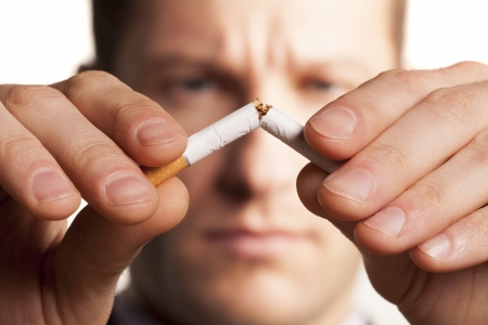aciculum: serious man with a blurred face breaks a cigarette