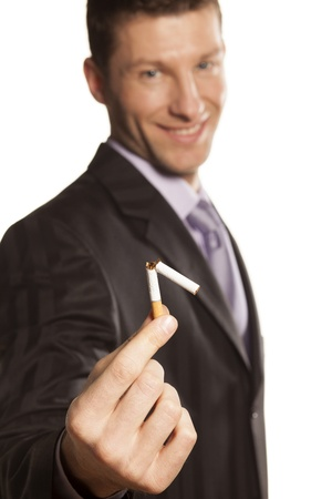 smiling handsome businessman holding a broken cigarette in his hand on white background