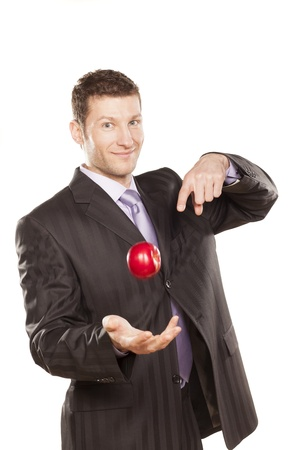 Businessman Tossing Apple on White Background photo