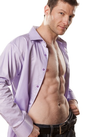 beau jeune homme athlétique avec un sourire et une chemise ouverte sur fond blanc