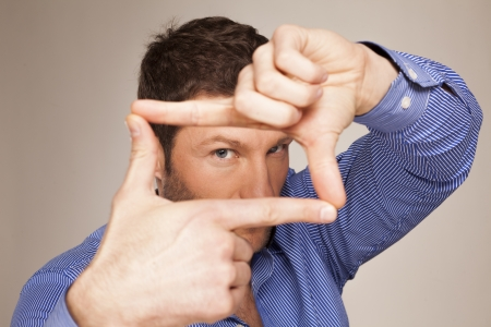 A man looking and focusing through his hands photo