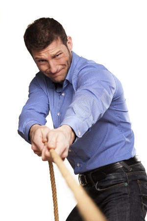 Young man pulling a rope on white background