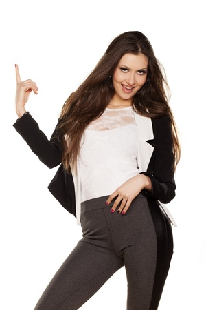 pretty brunette smiling and pointing a finger in the blank on white background Stock Photo - 18063886