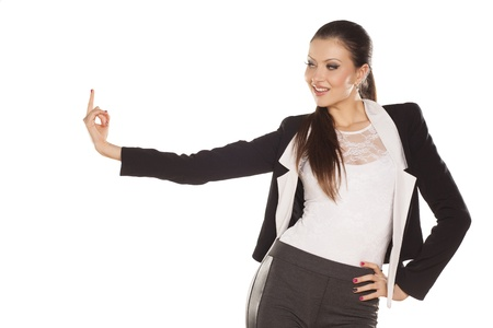 pretty brunette smiling and pointing a finger in the blank on white background Stock Photo - 18064155