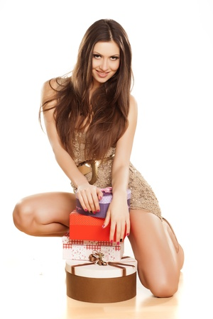 beautiful smiling brunette in a dress, kneeling with presents on white background photo