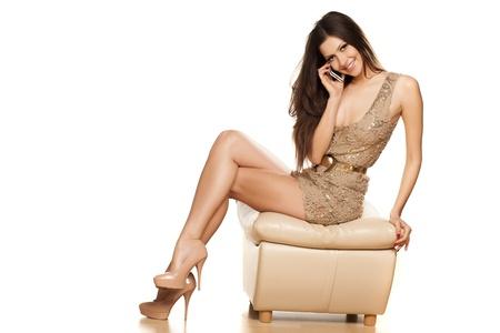 Sexy souriant assis brune et téléphoné dans une robe courte