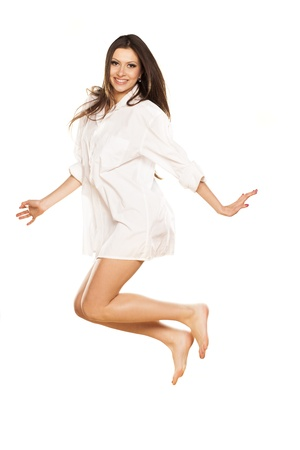 smiling attractive brunette in white shirt jumps photo
