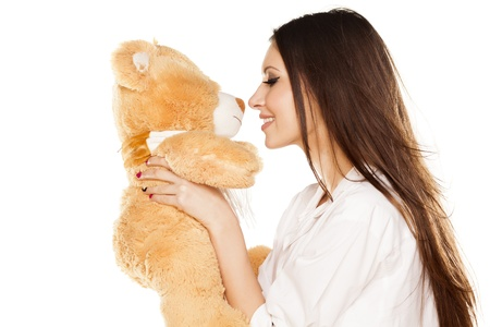 attractive smiling brunette kisses a teddy bear in a white shirt photo