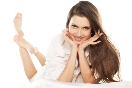 smiling attractive brunette lying on white sheets photo