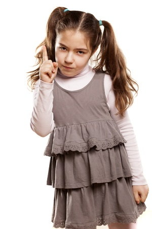 little finger: angry little girl shows a finger upwards on white background Stock Photo
