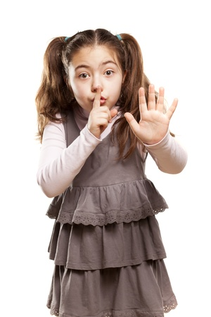 seus cute little girl shows a finger to her lips and stop hand Stock Photo - 18064037