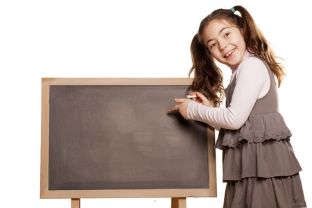 little girl girl standing next to a blackboard showing with finger to the board photo
