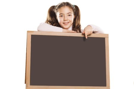 little girl leaning on a empty blackboard showing with finger to the board