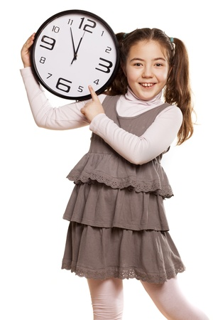 pre adolescent child: smiling little girl showing on the clock a little more time to start