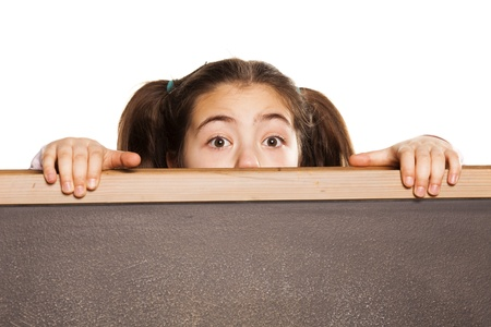 surprised little girl with tails peeks behind the blackboard on white background Stock Photo - 18063783