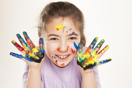 7 9 years: colors stained happy and smiling little girl showing ten fingers on white background