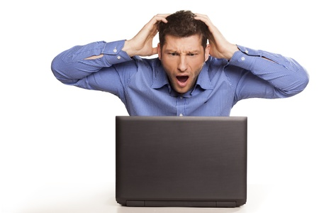 Man frustrated with his laptop computer on white background
