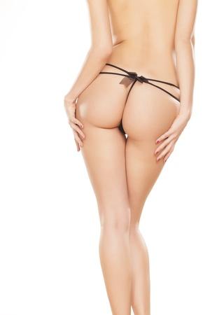 nalga: Espalda chica perfecta en tanga negro sobre fondo blanco Foto de archivo
