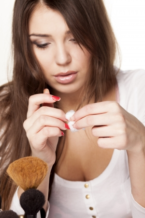 pretty girl using a cotton to removes her nail polish from her nails Stock Photo