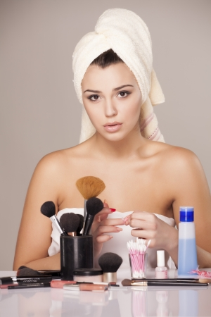 girl with towel on head using a cotton to removes her nail polish from her nails Stock Photo