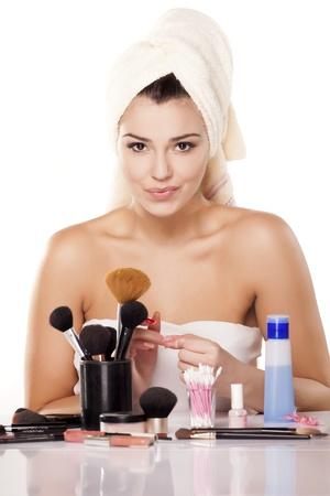souriante jeune fille avec une serviette sur la tête à l'aide d'un coton enlève son vernis à ongles de ses ongles
