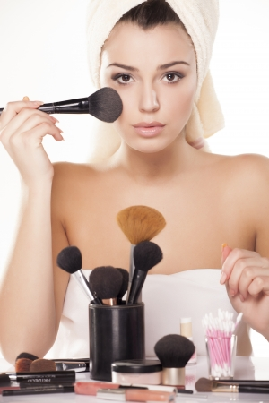 girl applied loose powder on her face with a brush for powder Stock Photo