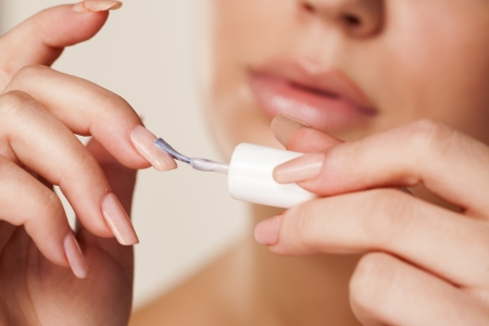 Close up of woman applying neutral nail polish