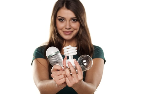 led lighting: Smiling girl shows all three generations of light bulbs Stock Photo