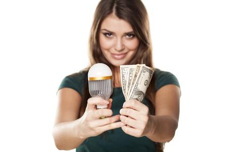 Sourire fille montre comment vous pouvez économiser de l'argent avec ampoule LED