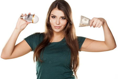 Smiling girl shows how you can save money with LED bulb Stock Photo