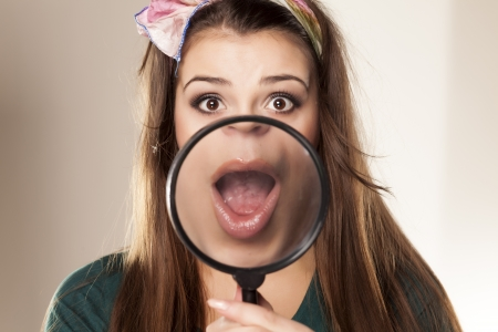surprised beautiful girl showing her mouth through a magnifying glass photo
