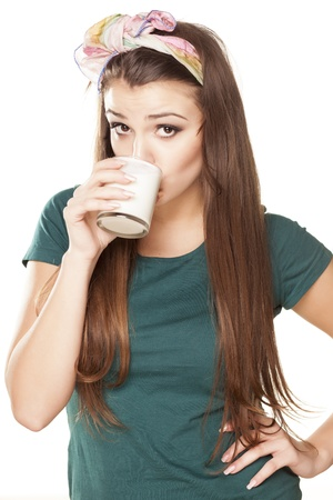 pretty happy girl in a green shirt with a pleased gesture drinking milk Stock Photo - 18195964