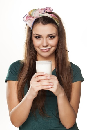 pretty happy girl in a green shirt with a pleased gesture drinking milk Standard-Bild