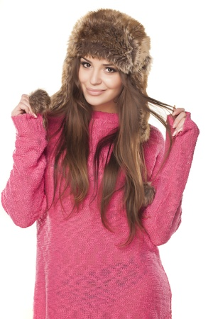 pretty and nice girl in a pink sweater and a fur hat posing on a white background photo