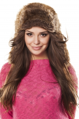 pretty and nice girl in a pink sweater and a fur hat posing on a white background Stock Photo - 18210473