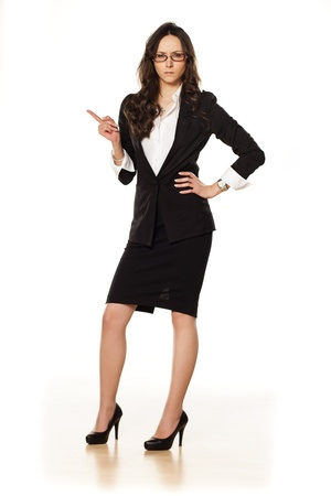 nervous business woman pointing a finger upwards photo