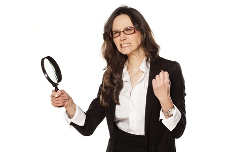 angry business woman is very upset with and a magnifying glass in hand photo