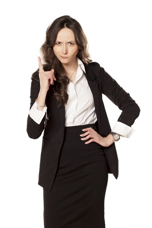 frowning and angry business woman pointing a finger upwards