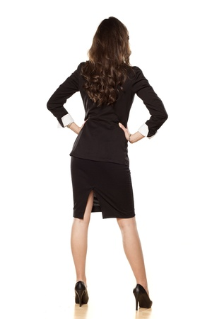 skirt suit: Rear view on the business woman in a skirt, high heels and suit