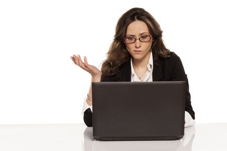 confused woman: confused girl with a laptop and do not know what to do further Stock Photo