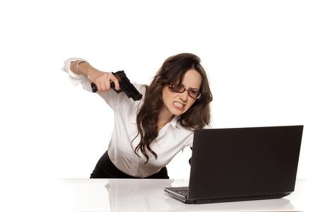 mujer con pistola: secretario nervioso y enojado destruye su ordenador port�til mediante el uso de armas de fuego Foto de archivo