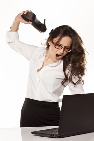 nervous and angry business woman destroys her laptop with high heels photo